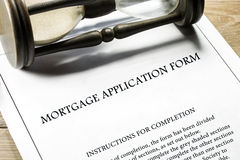 Legal series. Real estate mortgage application form, instructions for completion and hourglass in the background Royalty Free Stock Images