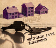 Legal series. Real estate mortgage loan agreement with house keys and three different blurred house models in the background Stock Image