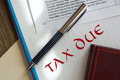 Legal series. Tax due on notebook page. Tax form and a stylish pen above Stock Image