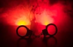 Legales Gesetzeskonzept Schattenbild von Handschellen mit der Statue von Gerechtigkeit auf Rückseite mit dem Blitzen rote und bla Lizenzfreie Stockfotos