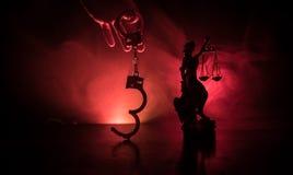 Legales Gesetzeskonzept Schattenbild von Handschellen mit der Statue von Gerechtigkeit auf Rückseite mit dem Blitzen rote und bla Lizenzfreie Stockfotografie
