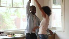 Legame ballante delle giovani coppie afroamericane romantiche felici nella cucina stock footage