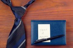 Legame del collo vicino al blocco note con la penna e l'autoadesivo giallo Immagine Stock