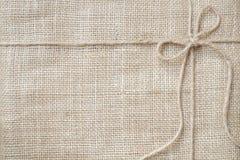 Legame del fondo della tela da imballaggio con la cordicella rustica della tela da imballaggio, prodotto naturale Fotografia Stock Libera da Diritti