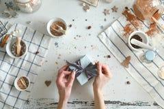 Legame di archi della donna dentro su regalo di Natale con il nastro blu Concetto di festa Vista superiore Fotografie Stock