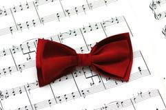 Legame di arco rosso sul documento di note musicali Fotografia Stock