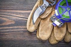 Legame di cavo molle dei guanti di sicurezza del pruner del giardino sul giardino del bordo di legno Fotografie Stock