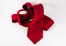 Legame di seta rosso sgualcito su fondo orizzontale bianco immagine stock