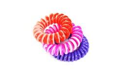 Legami elastici variopinti a spirale dei capelli isolati su un fondo bianco Fotografie Stock