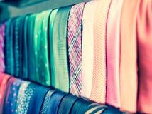 Legami sui ganci nel negozio di vestiti degli uomini Immagine Stock