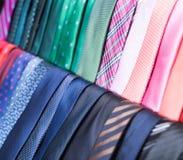 Legami sui ganci nel negozio di vestiti degli uomini Fotografia Stock Libera da Diritti