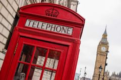 Legendary Phone Booth in London. The legandary vintage phone booth in center of London. Show also in the background the Big Ben. True logo of city of London Royalty Free Stock Images