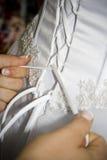 Legando sul vestito della sposa Fotografie Stock