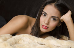 Legant exotic woman lying down on fur Royalty Free Stock Image