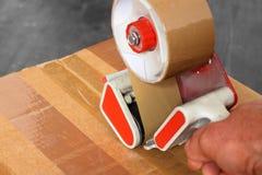 Legare l'erogatore con un nastro del nastro della scatola Fotografia Stock Libera da Diritti