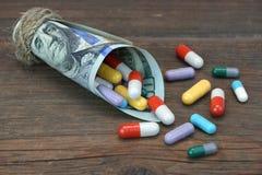 Legato con il dollaro Bill With Many Colorful Drugs della corda cento Immagine Stock Libera da Diritti
