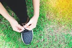 Legatura delle scarpe di sport sull'iarda, donna asiatica che si prepara per correre, sport all'aperto, esercizio, addestramento  Immagine Stock