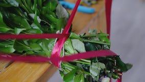 Legature del fiorista del mazzo rosso del nastro dei fiori Immagini Stock Libere da Diritti