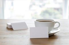 Lege adreskaartjes en kop van koffie op houten lijst Stock Afbeelding