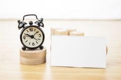 Lege adreskaartjespot omhoog en zwarte wekker op licht woode Royalty-vrije Stock Afbeelding