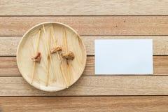 Lege bamboestok van geroosterde varkensvlees en document nota over houten schotel Stock Foto's