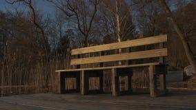 Lege bank op een houten dek door de kant van het water tijdens zonsonderganguren stock video