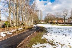 Lege Bedekte die Weg gedeeltelijk in Sneeuw op Sunny Winter Day wordt behandeld royalty-vrije stock fotografie