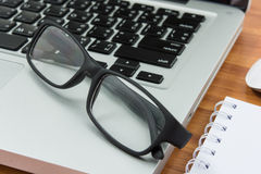 Lege bedrijfslaptop, muis, pen, nota en glazen Stock Foto