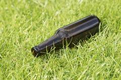 Lege bierfles in het gras Stock Foto's