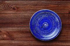 Lege blauwe plaat op donkere houten achtergrond stock foto