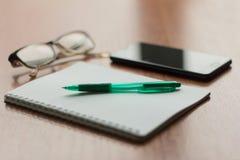 Lege Blocnote met pen en een telefoon op de Desktop royalty-vrije stock foto's