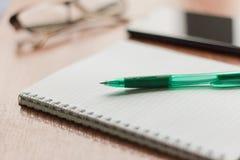 Lege Blocnote met pen en een telefoon op de Desktop stock afbeeldingen
