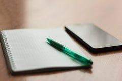 Lege Blocnote met pen en een telefoon op de Desktop stock afbeelding