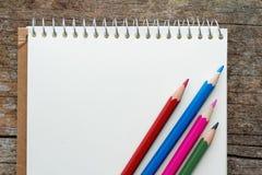 Lege blocnote met rode, blauwe, roze en groene kleurenpotloden op houten lijst Royalty-vrije Stock Afbeeldingen