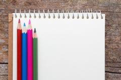 Lege blocnote met rode, blauwe, roze en groene kleurenpotloden op houten lijst Royalty-vrije Stock Fotografie