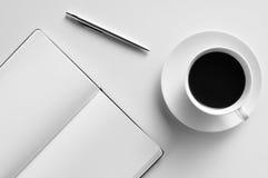Lege blocnote, pen en kop van koffie op een witte lijst stock afbeeldingen