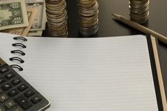 Lege blocnote, potlood, calculator en dollarbankbiljetten stock fotografie