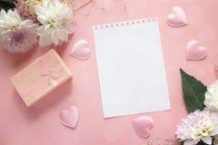 Lege blocnotepagina met dahlia's en giftvakje op een roze backgroun Stock Foto's