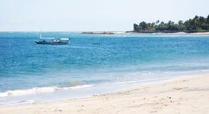 Lege boot bij een wit zandstrand en een duidelijke blauwe oceaan Royalty-vrije Stock Fotografie