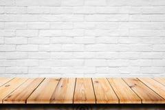 Lege bovenkant van houten lijst aangaande witte baksteenachtergrond stock afbeeldingen