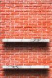 Lege bovenkant van witte marmeren plank met oude bakstenen muur stock afbeeldingen