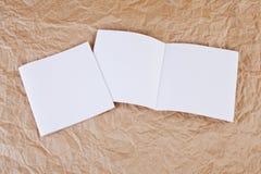 Lege brochures bij een bruine gerimpelde document achtergrond Stock Foto's