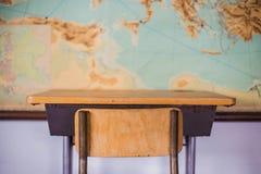 Lege bureaus bij schoolklaslokaal met wereldkaart stock foto
