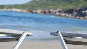 Lege Chaise Longue Under Sun Umbrella op de Oceaankust stock videobeelden