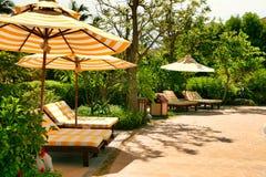Lege chaise zitkamers met geel-witte gestreepte matrassen die zich onder een zonparaplu met hetzelfde patroon bevinden Sanya, Hai stock foto