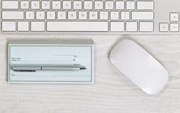Lege checkbook op witte Desktop met pen en muis stock afbeeldingen