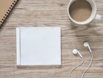 Lege compact disc, oortelefoons, notitieboekje en koffie op houten lijst stock foto's