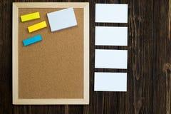Lege cork raad met houten kader en blocnote kleverig document op w Stock Afbeeldingen