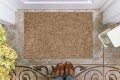 Lege deurmat vóór de deur in de zaal Mat op ceramische vloer, bloemen en schoenen Welkom huis, productmodel royalty-vrije stock foto's