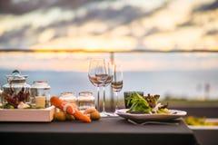 Lege die glazen in restaurant - Dinerlijst in openlucht bij zonsondergang worden geplaatst Royalty-vrije Stock Fotografie